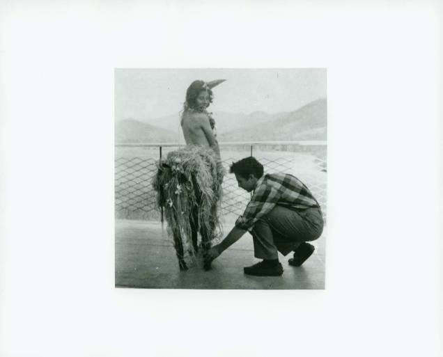 Robert_Rauschenberg_kneeling_to_adjust_centaur_costume_worn_by_Svarc_Lauterstein_Black_Mountain_College_1949